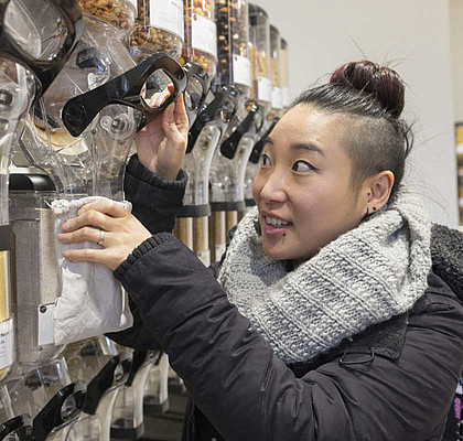 Shia Su aus Bochum füllt sich in einem unverpackt-Laden Lebensmittel ab.