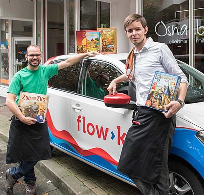 Die Mitarbeiter von Osnabrett Artur Baginski und Andy Petsch mit Brettspielen und einem Carsharing-Auto.