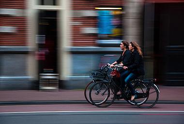 Zwei Frauen fahren Fahrrad. E-Bikes sind eine saubere und bequeme Alternative zum Auto.