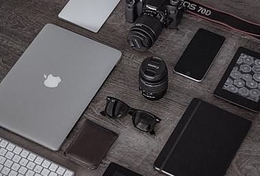 Unterhaltungselektronik verbraucht im Betrieb und bei der Herstellung viel Energie und CO2: Tablet, Kamera, Handy und andere Elektronik auf einem Tisch.