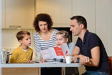 Eine Familie vergleicht ihre Heizkosten mit Hilfe des Heizspiegel-Flyers.